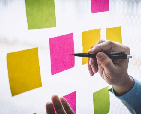hombre-negocios-usa-notas-publicar-idea-planificacion-estrategia-marketing-comercial-nota-adhesiva-pared-vidrio_122498-138